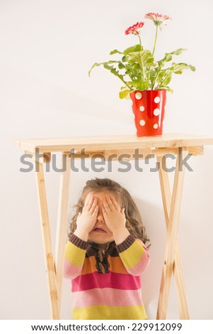 Cute little girl hiding under the table covering her face with her hands, red vase with flower on table, studio shot, on white background. Little girl is playing hide-and-seek hiding face - stock photo