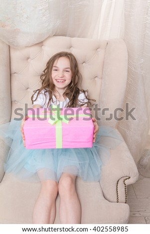 Cute little girl hold giftbox, sit in chair, astonished face expression - stock photo