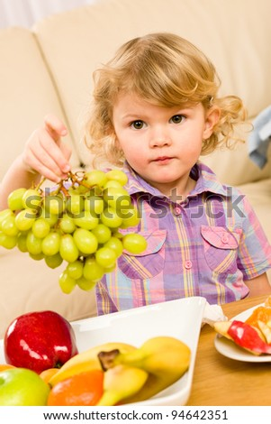 Cute little girl hold grapes healthy fruit bowl at home