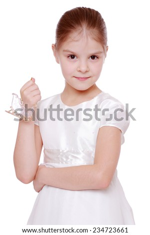 Cute little girl holding a Christmas decoration in the form of skates