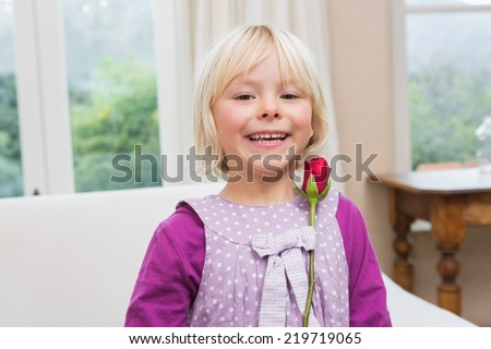 Cute little girl holding a red rose at home in the living room