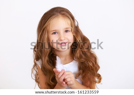 Cute little girl holding a white feathers on white background - stock photo