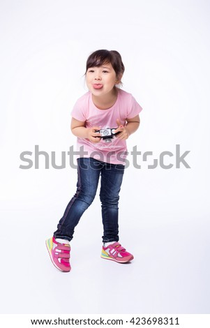 cute little girl holding an old camera. child taking pictures on an old camera. the child plays the fool - stock photo