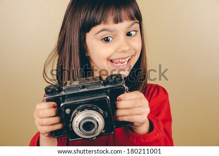 Cute little girl holding an old medium format camera with a funny expression. Some film grain and vintage effect added - stock photo