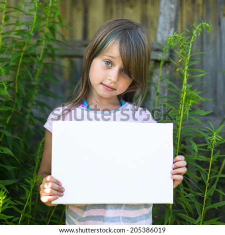 Cute little girl holding clean white sheet paper, outdoors (banner for your message) - stock photo