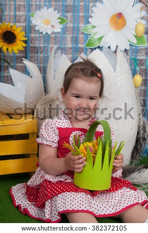 Cute little girl holding flowers. Studio portrait. Mother's Day, March 8, International Women's Day.Girl in the interior decorations to the day of Easter. spring portrait girl with bouquet of flowers - stock photo