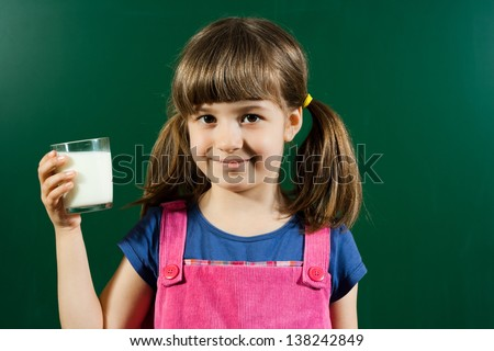 Cute little girl holding glass of milk in front of blackboard,Little girl with glass of milk - stock photo