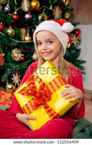 Cute little girl holding her gift in front of christmas tree - stock photo