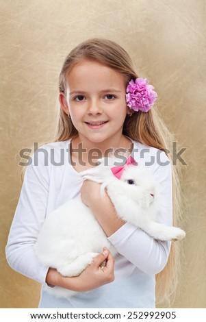 Cute little girl holding her white rabbit - portrait on golden background- shallow depth of field - stock photo