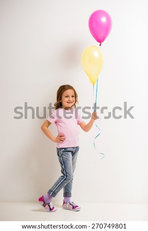 Cute little girl holding pink and yellow balloons on grey background. - stock photo
