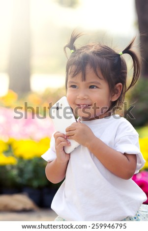 Cute little girl holding smart phone in flower garden