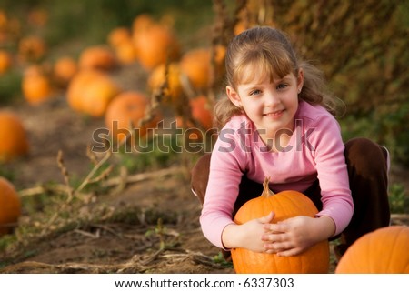 Cute little girl hugging a pumpkin in a pumpkin patch.