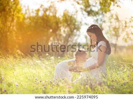 Cute little girl hugging and kissing her mother's pregnant belly in summer nature - stock photo