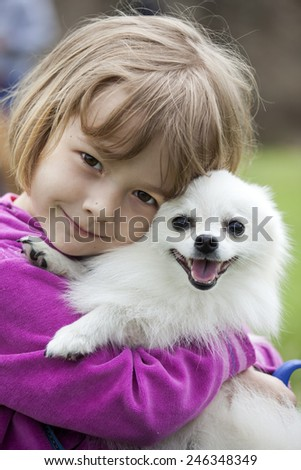 Cute little girl hugging dog - stock photo
