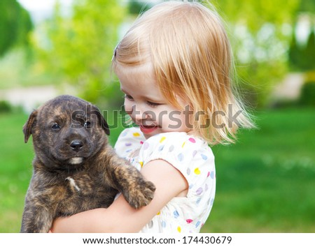 Cute little girl hugging dog puppy. Friendship and care concept - stock photo