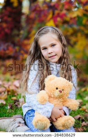 Cute little girl hugging teddy bear toy at autumn background