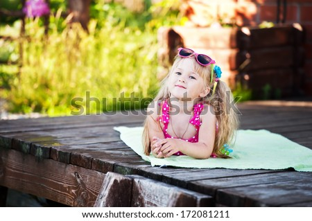 cute little girl in a bathing suit is tans and dreams - stock photo