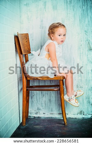 Cute little girl in a beautiful white dress sitting on the old chair by the white brick wall. Childhood. - stock photo