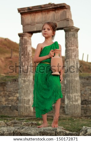 cute little girl in a bright emerald green dress standing in the ruins of the ancient city in the role of the Greek goddess - stock photo