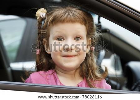 Cute little girl in a car - stock photo
