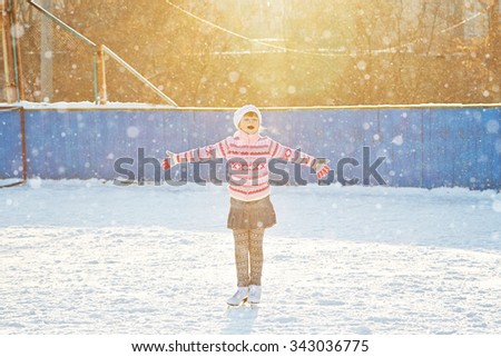 cute little girl in a hat and a sweater ice skating. child winter outdoors on ice rink - stock photo