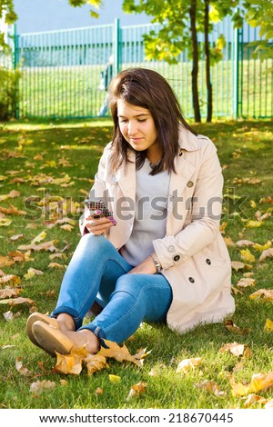 Cute little girl in a light coat and jeans sits on a lawn, talking on the phone - stock photo