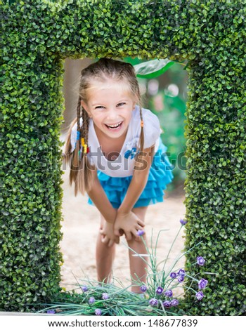 cute little girl in a park near the bush - stock photo