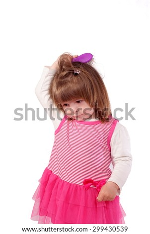Cute little girl in a pink dress brushing her hair  white background