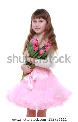 Cute little girl in a pink tutu holding a bouquet of pink tulips on white background