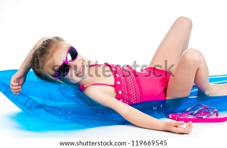 cute little girl in a swimming suit on an inflatable mattress - stock photo