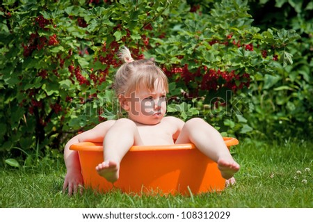 Cute little girl in a tub in a summer garden with berries in the background - stock photo