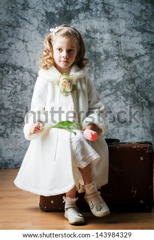 Cute little girl in a white coat sitting on an old suitcase. Retro style