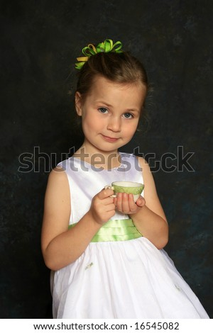 Cute little girl in a white dress holding a tea cup - stock photo