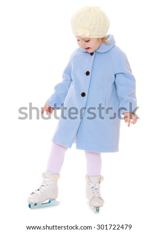 Cute little girl in a white tracksuit standing on the ice in a blue woolen coat. On the feet of the girls are wearing skates. Girl in school figure skating choreography. Her mom every day goes to - stock photo
