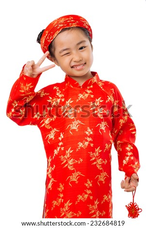 Cute little girl in ao dai dress winking and showing two fingers