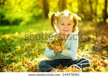 Cute little girl in autumn park holding bunch of yellow leaves - stock photo