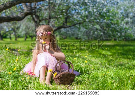 Cute little girl in blossoming apple garden at sunny spring day - stock photo