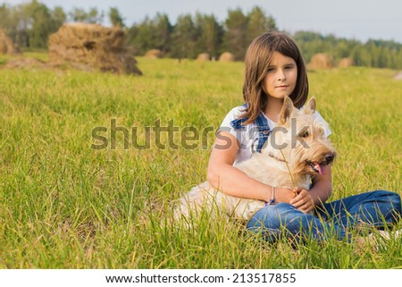 Cute little girl in blue jeans with her dog Scottish Terrier sitting in a field in summer - stock photo