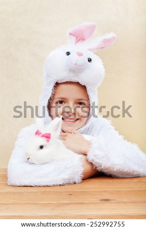 Cute little girl in bunny costume holding her white rabbit - laughing with joy - stock photo
