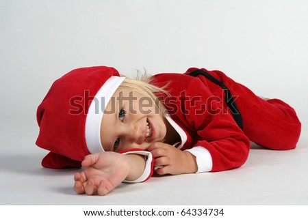 Cute little girl in Christmas hat and dress - stock photo