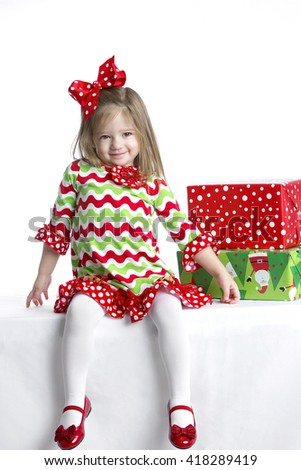 Cute little girl in colorful Christmas dress with gifts on table