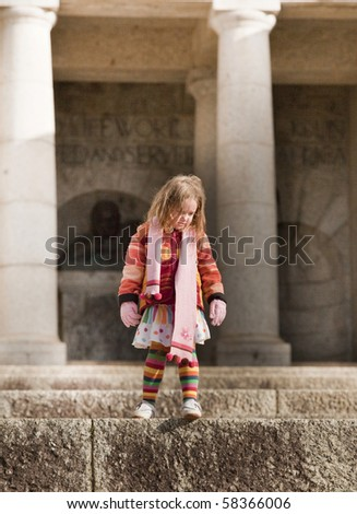 Cute little girl in colorful winter clothes on the steps of an official looking building.