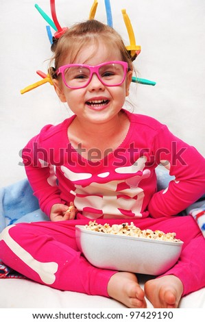 Cute little girl in curler eating popcorn and watching TV - stock photo