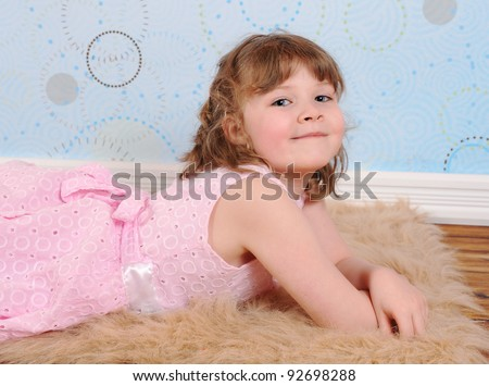 cute little girl  in dress laying on a furry brown rug smiling - stock photo