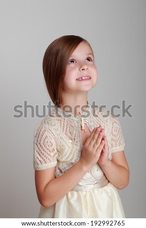 Cute little girl in dress think, dream looking up/Caucasian adorable princess on grey background - stock photo