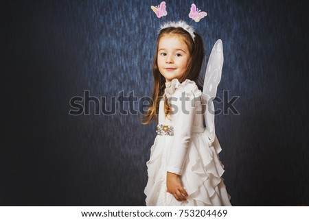 Cute little girl in fairy costume have fun and shows different emotions on dark blue background. Studio portrait, close up.
