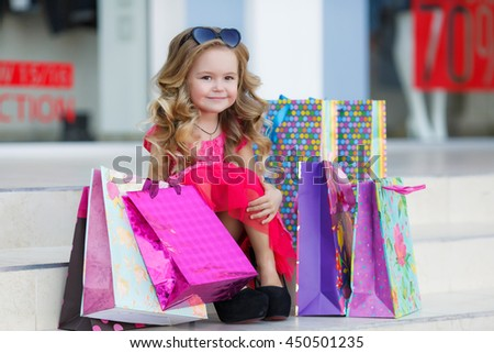 cute little girl in fashionable hat on shopping. portrait of a kid with shopping bags. child in dress, sunglasses and shoes near shopping mall having fun. shopping. girl. fashion - stock photo