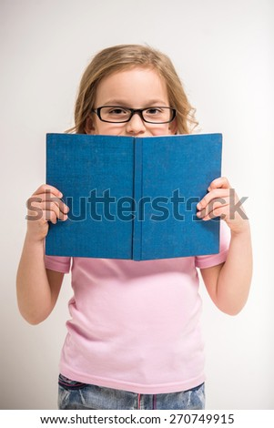 Cute little girl in glasses is holding a book  on grey background. - stock photo