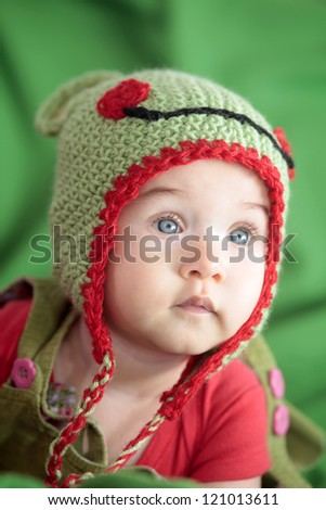 Cute little girl in hand knit hat - stock photo