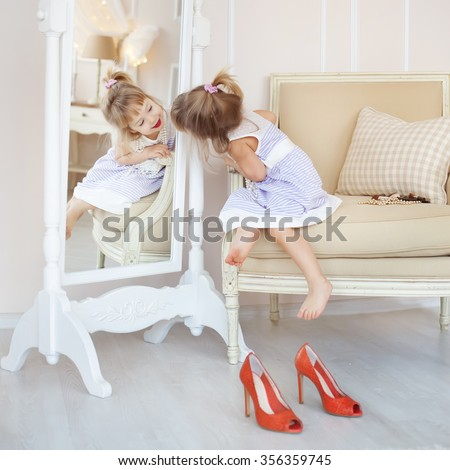 Cute little girl in her mother's room, using makeup to imitate adults - stock photo